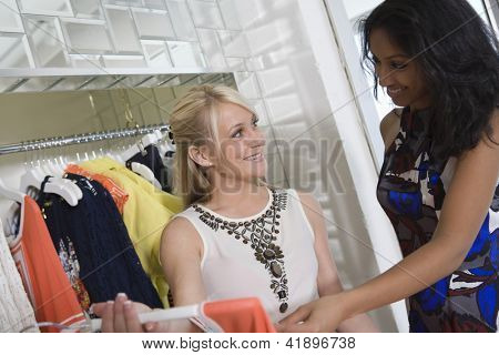 Owner of a fashion store assisting young trendy woman selecting clothes