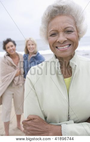 Portrait of happy African American senior woman with friends in the background