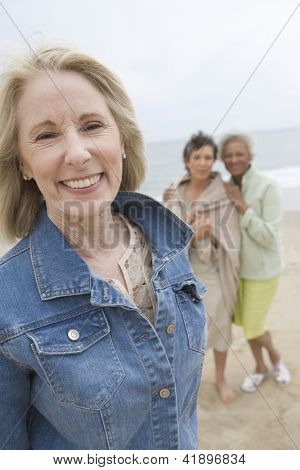 Portrait of happy senior woman with friends at beach
