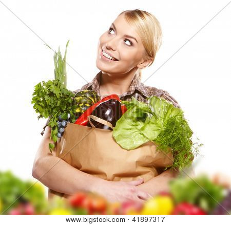 Portrait of happy young woman holding a shopping bag full of groceries on white background