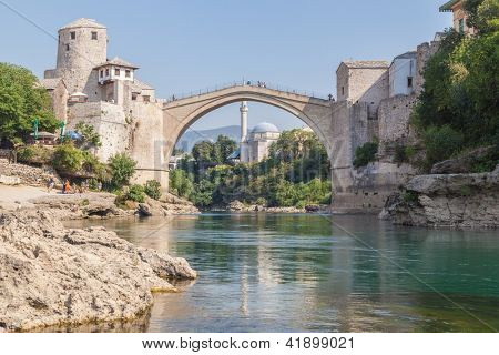 MOSTAR, BOSNIA - AUGUST 10: The Old bridge and town on the Neretva River on August 10, 2012 in Mostar, Bosnia. The river separates the Catholic Bosnian Croats from the Bosnian Muslims.