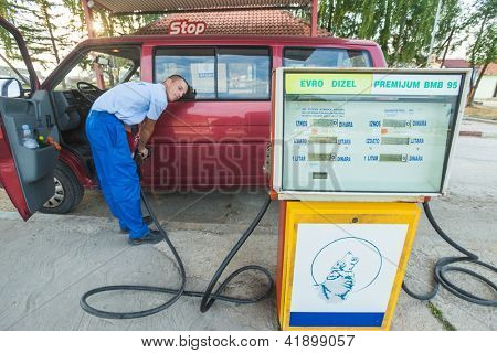 BELGRADE, SERBIA - AUGUST 16: Young man refuelling on August 16, 2012 near Belgrade, Serbia. Most gas stations in the Balkan region are self-service, but Serbia still maintains personal service.