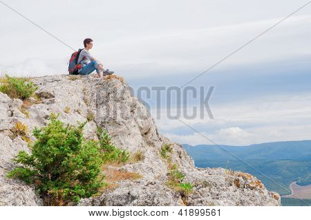 irl sitting on a mountain and looking on the valley