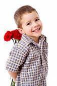 stock photo of carnation  - Smiling boy hiding a bouquet of red carnations behind itself - JPG