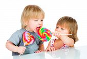 image of lollipop  - Babies eating a sticky lollipop on white background - JPG