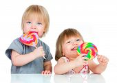 stock photo of lollipop  - Babies eating a sticky lollipop on white background - JPG