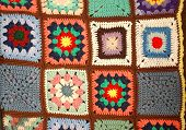 pic of stitches  - A vertically hung section of a crochet knit quilt showing squares with different colors and patterns - JPG