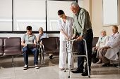 picture of zimmer frame  - Senior man being helped by female nurse to walk the Zimmer frame with people sitting in hospital lobby - JPG