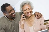 picture of beside  - Happy senior African American woman on call while holding credit card with man besides her - JPG