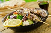 stock photo of spit-roast  - A delicious grilled pork souvlaki served with greek salad - JPG