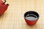 Japanese cup of tea with a tetsubin on a bamboo mat - a traditional cast iron red hobnail design wit