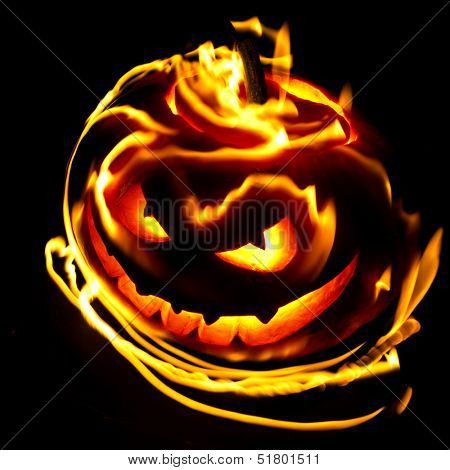 Burning halloween pumpkin on black background