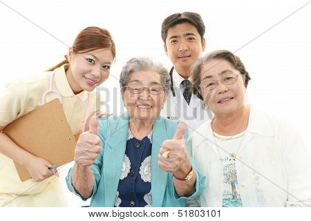 Smiling Asian medical staff with old women