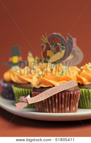 Happy Thanksgiving Cupcakes With Turkey, Feast, And Pilgrim Hat Topper Decorations Against A Harvest
