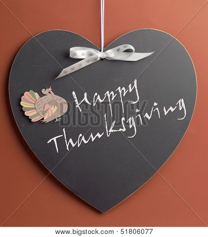 Happy Thanksgiving Message Written On Heart Shape Blackboard With Turkey Motif Decoration.