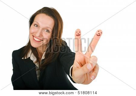 Friendly attractive young woman with a lovely smile holding up her fingers in a V-sign with two little Smiley faces drawn on them, conceptual image isolated on white