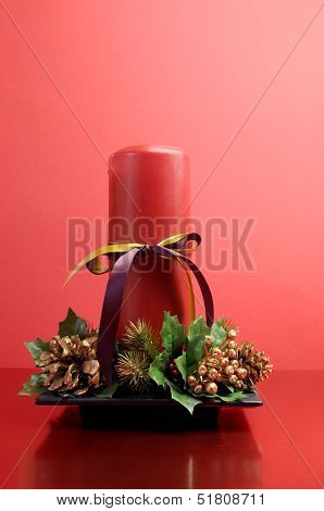 Red Candle With Holly And Pine Cone Christmas Table Centrepiece Still Life Against A Festive Holiday