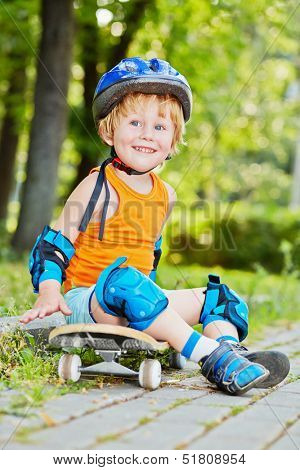 Smiling little boy in protective equipment sits on skateboard on walkway at park
