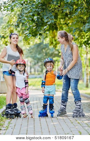 Two smiling teen girls in rollers hold hands of two kids roller beginners