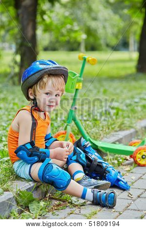 Little scooterist in protective equipment rests sitting on curb of walkway in park and eating cracker