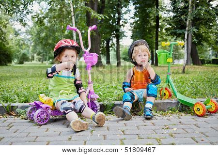 Children scooterists rest sitting on curb of walkway in park ant eat crackers