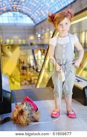 Little pretty girl with dog on leash stands next to escalator in mall.