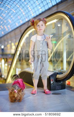 Little girl with cell phone and small dog on leash stands next to escalator in mall.