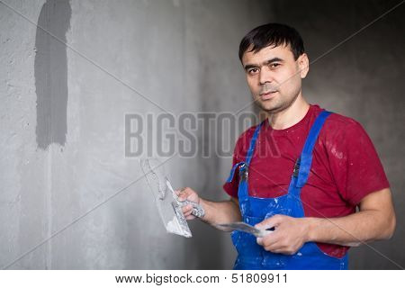 A worker makes repairs smears on the wall putty