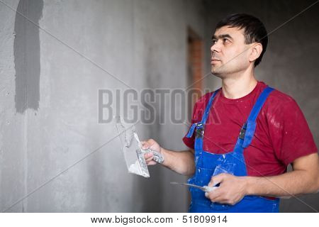 A worker with spatula in workwear smears on the wall putty