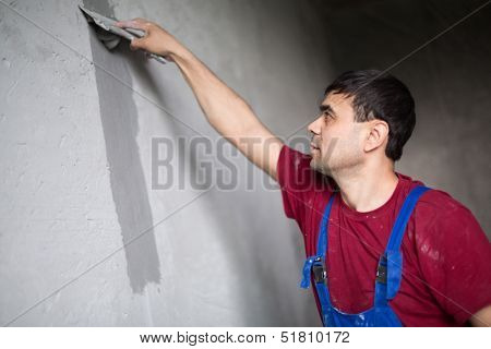 A worker with spatula makes repairs smears on the wall putty