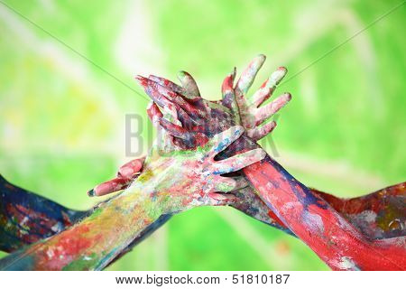 Interlacing female and male hands in the paint of different colors make a figure