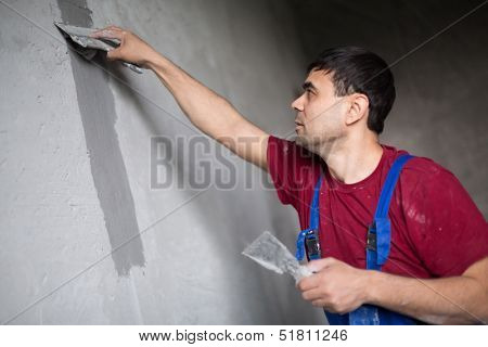 A worker with spatula in workwear makes repairs smears on the wall putty