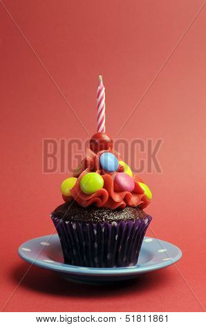 Candy Covered Chocolate Cupcake With Red Frosting And Candy And One Birthday Candle On Red Backgroun