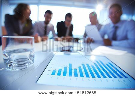 Close-up of business document in touchpad lying on the desk, office workers sitting in the background