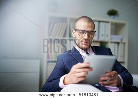 Portrait of businessman with touchpad working in office