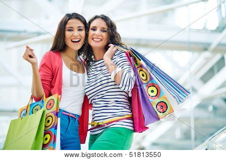 Joyful girls with paperbags looking at camera in trade center