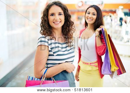 Gorgeous female with paperbags looking at camera with her friend on background