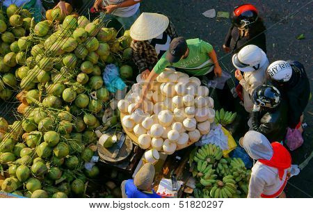People buy and sell coconut at open air market