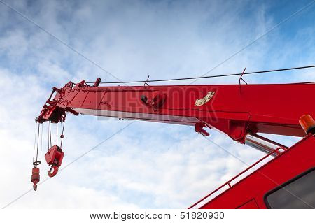 Red Truck Crane Boom With Hooks And Scale Weight Above Blue Sky
