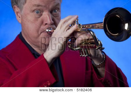 Senior Man Musician Playing Trumpet On Blue