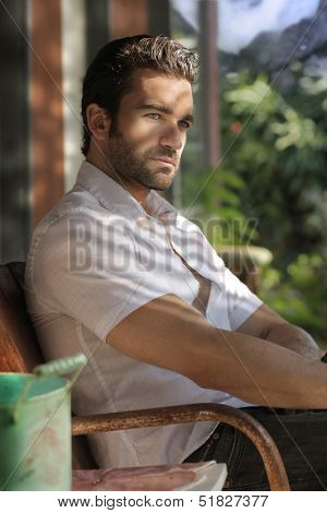 Portrait of a great looking masculine man relaxing on a front porch