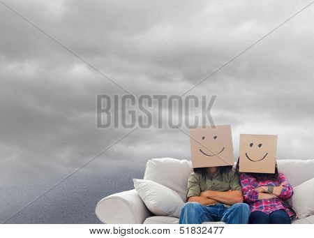 Composite image of silly employees with arms folded wearing boxes on their heads floating in cloudy sky