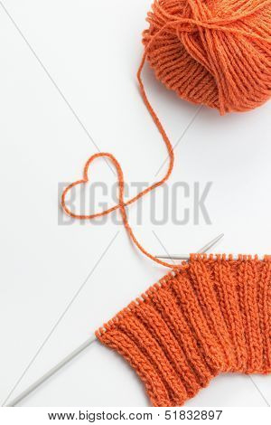 Incomplete knitting project with ball of orange wool