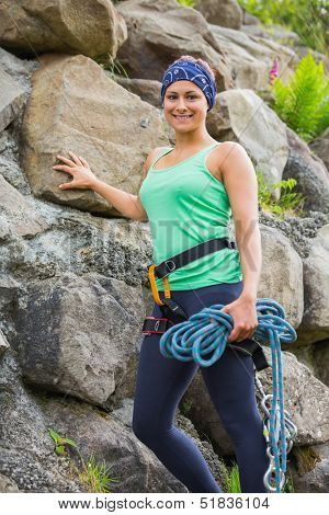 Attractive female rock climber smiling at camera leaning on rock face