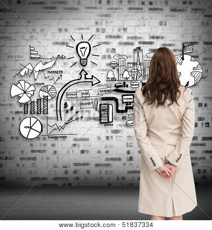 Composite image of rear view of businesswoman crossing hands behind back looking at economic illustrations on grey wall