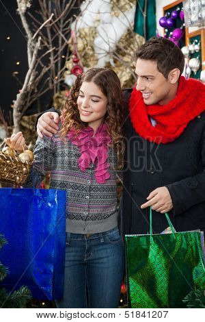 Happy young couple with bags and bauble basket shopping in Christmas store