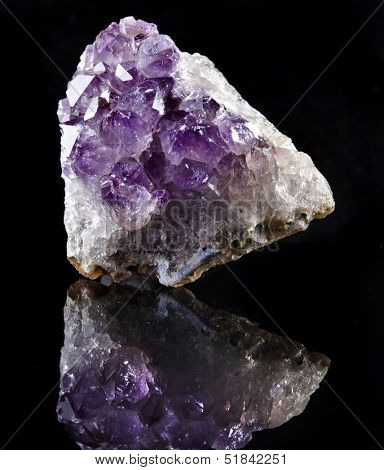 Natural cluster of Amethyst, violet variety of quartz close up macro with reflection isolated on black background