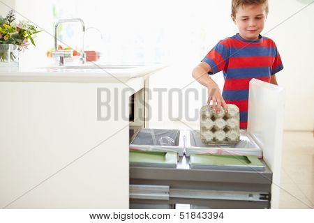 Boy Recycling Kitchen Waste In Bin