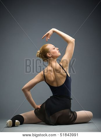 Backview of dancing on the floor ballerina with hands up, isolated on white on grey. Concept of elegant art and sportive hobby