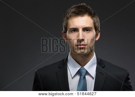 Front view of self-confident business man in dark suit with black tie. Concept of professionalism and success in business
